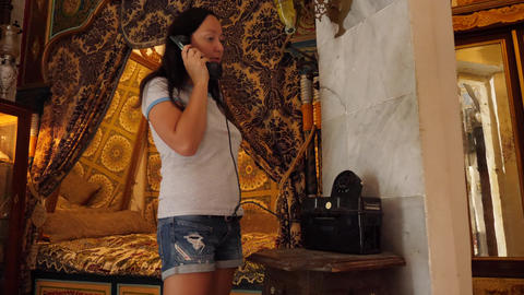 Woman calling by retro phone at bedroom in vintage style interior Live Action