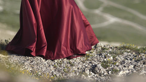Young girl holds the hem of the purple dress in the wind The folds of the fabric Footage