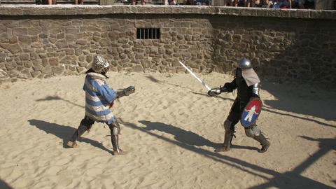Two armored gladiators making a show with a fight on sandy arena Real Rumble Live Action