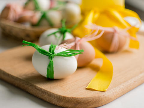 Close-up of Easter eggs tied with ribbon on white background Photo