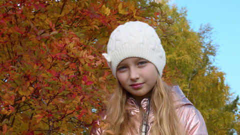 Serious girl on autumn orange leaves background. Smiling girl in autumn park Footage