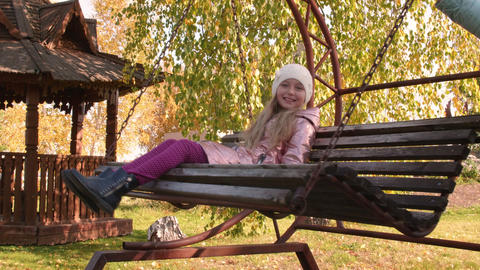 Happy girl swinging in autumn park. Smiling girl enjoying autumn nature Live Action