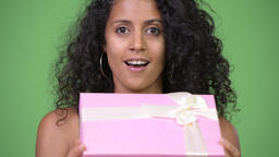 Young beautiful Hispanic woman looking surprised while opening gift box Footage