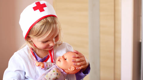 little girl is playing doctor. A child in a doctor's suit soothes a toy doll Live Action
