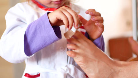 Pretty little girl is trying to be doctors. A child in the suit of a doctor ビデオ