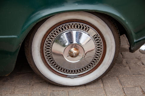Wheel of a retro car standing on the street Photo