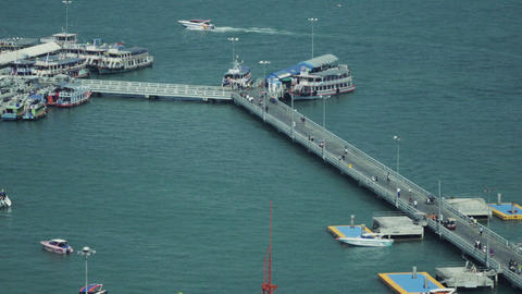 People crossing the bridge between harbor and waterfront at Pattaya pier Footage