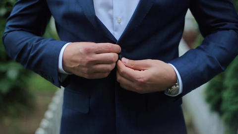 Buttoning a Jacket. Stylish Man in a Suit Fastening Buttons on His Jacket Prepar GIF