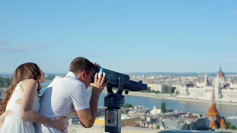 Young Man With Woman At The Viewing Point Using Coin Operated Binocular To See T stock footage
