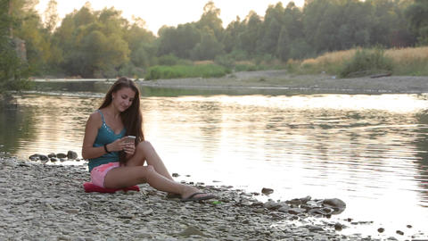 Girl Sitting on the River Bank of Phone Viewing Mail Footage