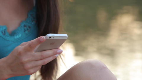 Girl Sitting on the River Bank With the Phone Viewing Photos Footage