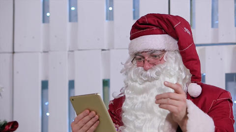 Santa Claus Flipping Page on Digital Tablet in Room with Christmas Tree and Gift Footage