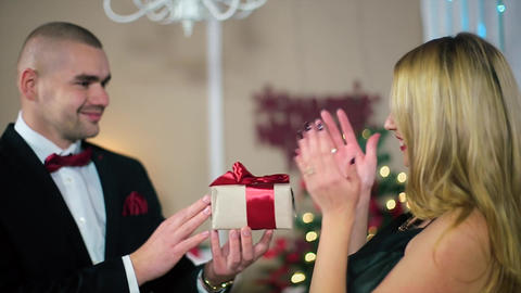 Man in a Black Suit Gives a Woman in Evening black dress a gift with a red ribbo Footage
