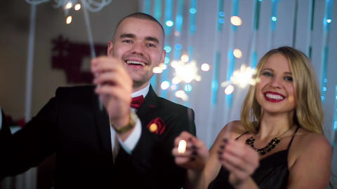a Man in a Black Suit and a Woman in Evening Black dress waving sparklers, in a  Footage