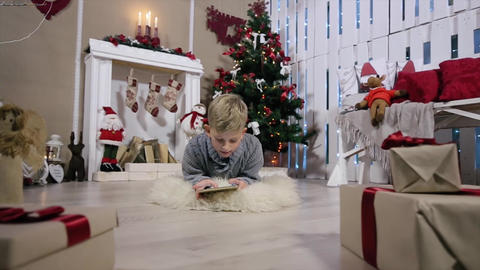 The boy chooses a gift for the digital tablet, the camera moves to a boy, white  Footage