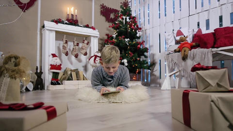 Laughing boy playing on digital tablet, The camera moves on a boy, white Room wi Footage
