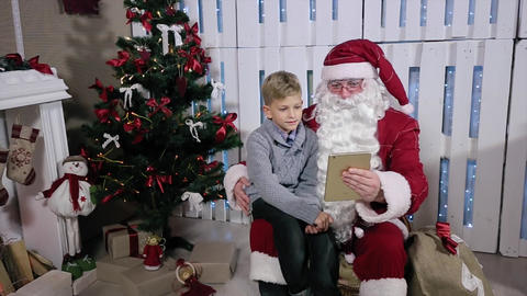 Santa and Little Boy Choose Gifts on Tablet, Sit Near a Christmas Tree with Gift Live Action