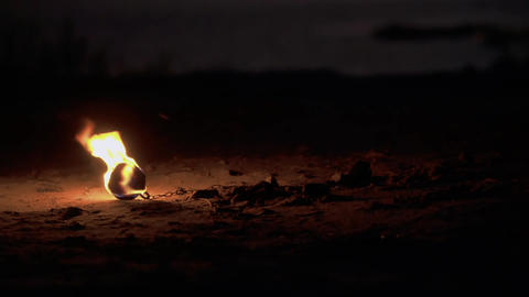 Human torches a torch from a burning poi lying on the ground Live Action