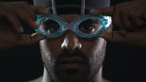 Serious face of Hispanic swimmer wearing goggles and looking into camera, sport Footage