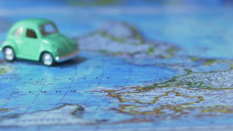 World map poster laid out across table, toy car crossing it, travel by auto Live Action