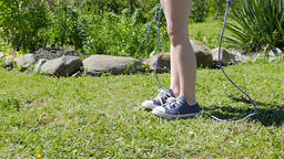 The Girl Is Jumping On The Rope On The Grass.Close Up. Slow Motion 2 GIF