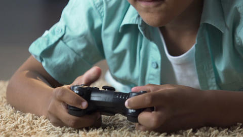 Little child lying on floor with play station control playing video games, anger Live Action