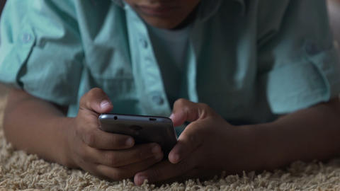 Biracial boy on floor with mobile phone, pressing on screen, gadgets addiction Live Action