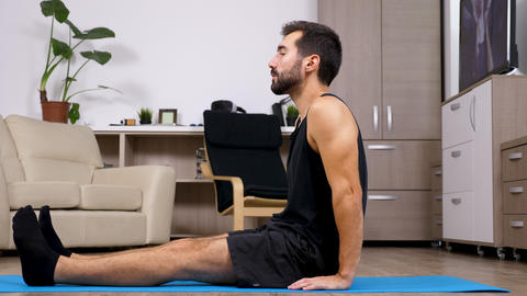 Man relaxing in different yoga poses on a blue mat Footage