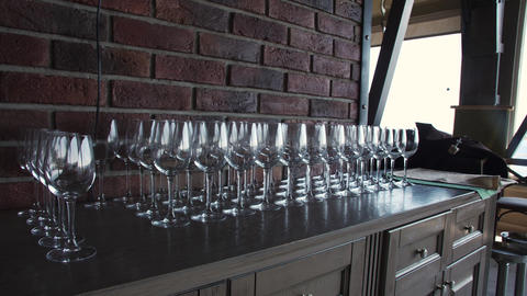 Empty wine glasses stand in a row at a banquet table indoors Footage
