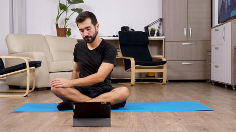 Man repeating exercises after what he sees on a digital tablet PC Footage