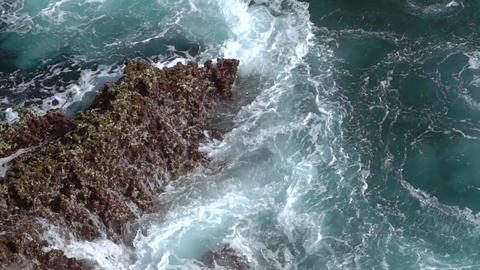 Surf Wave Rages near the Rock. Slow Motion Footage
