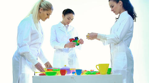 Womens in Laboratory Check Quality of Plastic Toys in White Room Footage