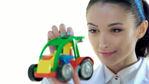 Woman Employee to Look at the Color Plastic Toy Tractor Footage