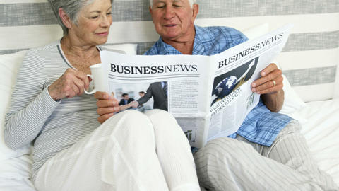 Happy senior couple reading a newspaper Footage