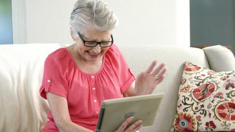 Senior woman using digital tablet in living room Stock Video Footage