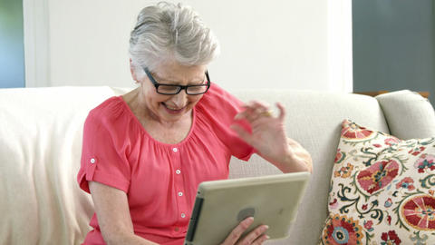 Senior woman using digital tablet in living room Live Action