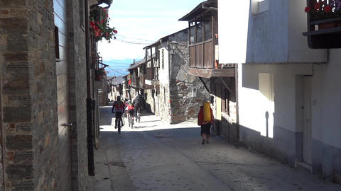 Group of bicyclists going on a narrow street lined by stone houses with a floor  Footage