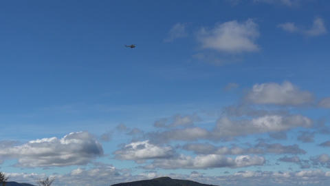 Military helicopter flying against a blue sky with fluffy clouds and gray 35a Footage