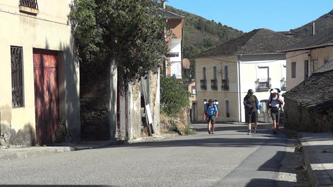 Pilgrims with luggage in the back going on a paved road through the houses of a  Footage