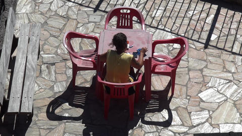 Woman sits at a plastic table, red seated on the terrace and write letters to lo Footage