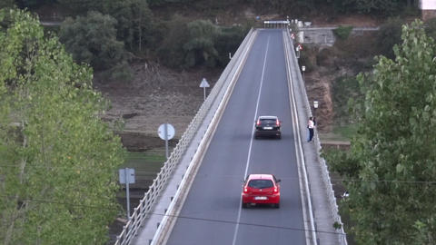 Cars crossing a concrete bridge while some pedestrians are leaning against the r Footage