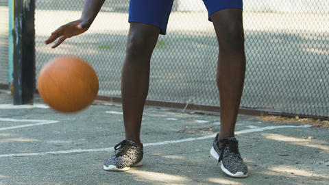 African American man skillfully handling ball before throwing, slow-motion Footage