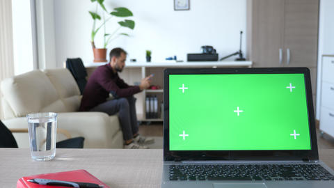 Laptop with green screen chroma on it in the middle of living room Footage