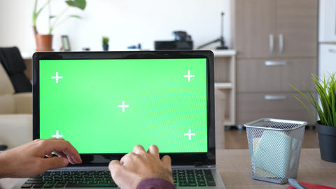 Revealing shot of man working on the computer with a chroma green screen mock up Live Action