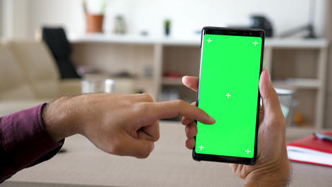 Man using a modern smartphone with green screen chroma mock-up in his living Footage