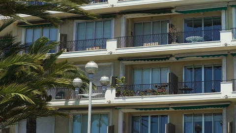 House balconies with awnings swaying in wind, real estate in sunny resort city Live Action