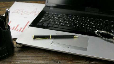 Slider shot, close-up of desktop, laptop, pen and glasses Footage