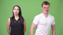 Young nerd man farting beside young Asian businesswoman Footage