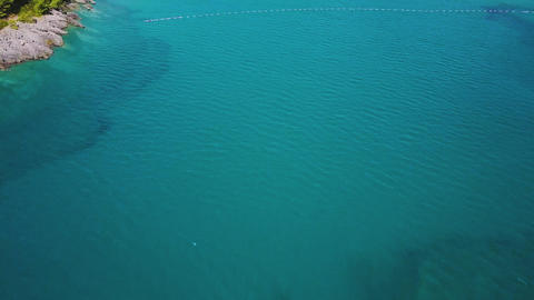 Flying above clear sea waters to white sandy beach circled with forest. Aerial Live Action