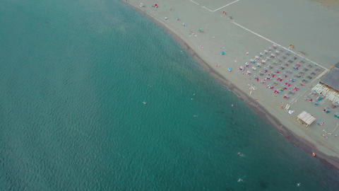 Flying along long sandy beach. Swimming and sunbathing people from above GIF